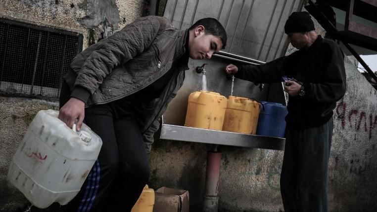 Des Palestiniens remplissent des bouteilles et des jerricanes d'eau potable à des robinets publics au camp de réfugiés de Rafah dans le sud de la bande de Gaza, le 22 février 2017 (Crédit : Said Khatib/AFP)