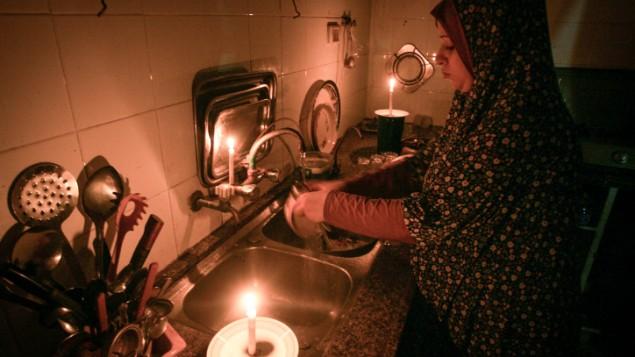 Une femme palestinienne fait la vaisselle à la lumière de la chandelle dans le camp de réfugiés de Rafah, dans le sud de la bande de Gaza, le 12 juin 2017 (Crédit : Abed Rahim Khatib / Flash90)