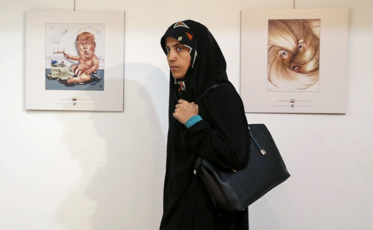 An Iranian woman looks at cartoons of US President Donald J. Trump at an exhibition of the Islamic Republic's 2017 International Trumpism cartoon and caricature contest, in the capital Tehran on July 3, 2017. (AFP PHOTO / ATTA KENARE)