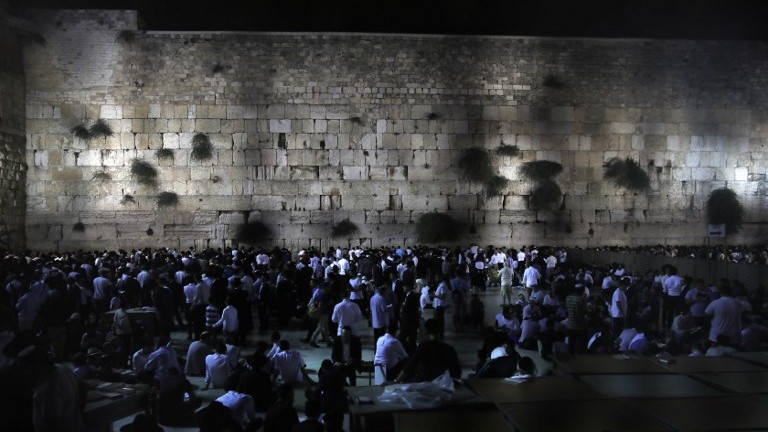 Jewish men pray at the Western Wall in Jerusalem's Old City during the annual Tisha B'Av fast day commemorating the destruction of the Jewish temples, on July 31, 2017. (AFP Photo/Menahem Kahana)