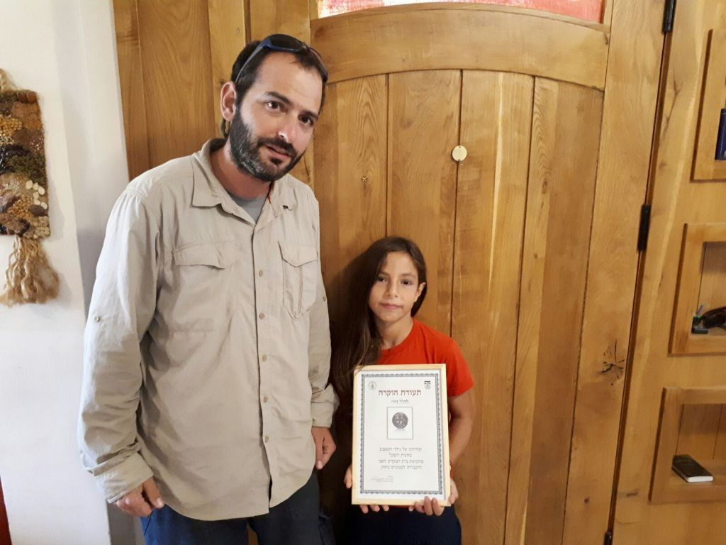 8-year-old Hallel Halevy with the Civil Administration archaeologist who collected the 2,000-year-old half-shekel coin from her home in Neve Tsuf, August 23, 2017. (courtesy)