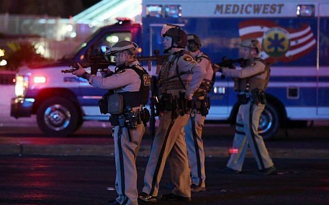 Des policiers pointent leurs armes sur une voiture qui roule sur Tropicana avenue, bouclée, près de Las Vegas Boulevard, après que des coups de feu ont étés entendus durant un festival de musique country, le 2 octobre 2017, à Las Vegas, dans le Nevada. (Crédit : Ethan Miller/Getty Images/AFP)