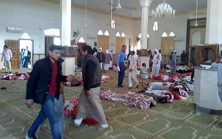 Des Egyptiens marchent autour des cadavres suite à un attentat à l'arme à feu et à la bombe commis dans la mosquée de  Rawda, à à peu-près 40 kilomètres à l'ouest de la capitale d'el-Arish, dans le nord du Sinaï, le 24 novembre 2017 (Crédit : AFP PHOTO / STRINGER)