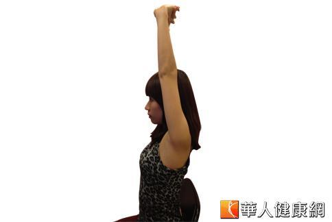 第1招:坐在椅子上,雙手手指相扣反掌,吸氣向上伸展。(攝影/黃子倫)