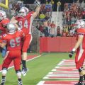 Stony Brook's Miguel Maysonet celebrates one of his four touchdowns along with Mike Lisi, 65, and Brett Arce, 84, during Stony Brook's homecoming victory over Lafayette at Kenneth P. LaValle Stadium on Sept. 24, 2011. Photo by Kevin Lizarazo.