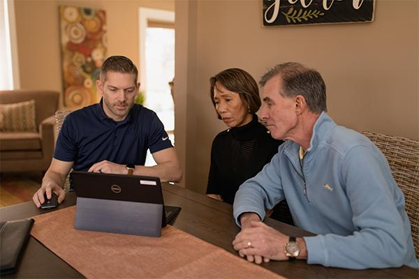The picture shows a contractor meeting with a young couple.