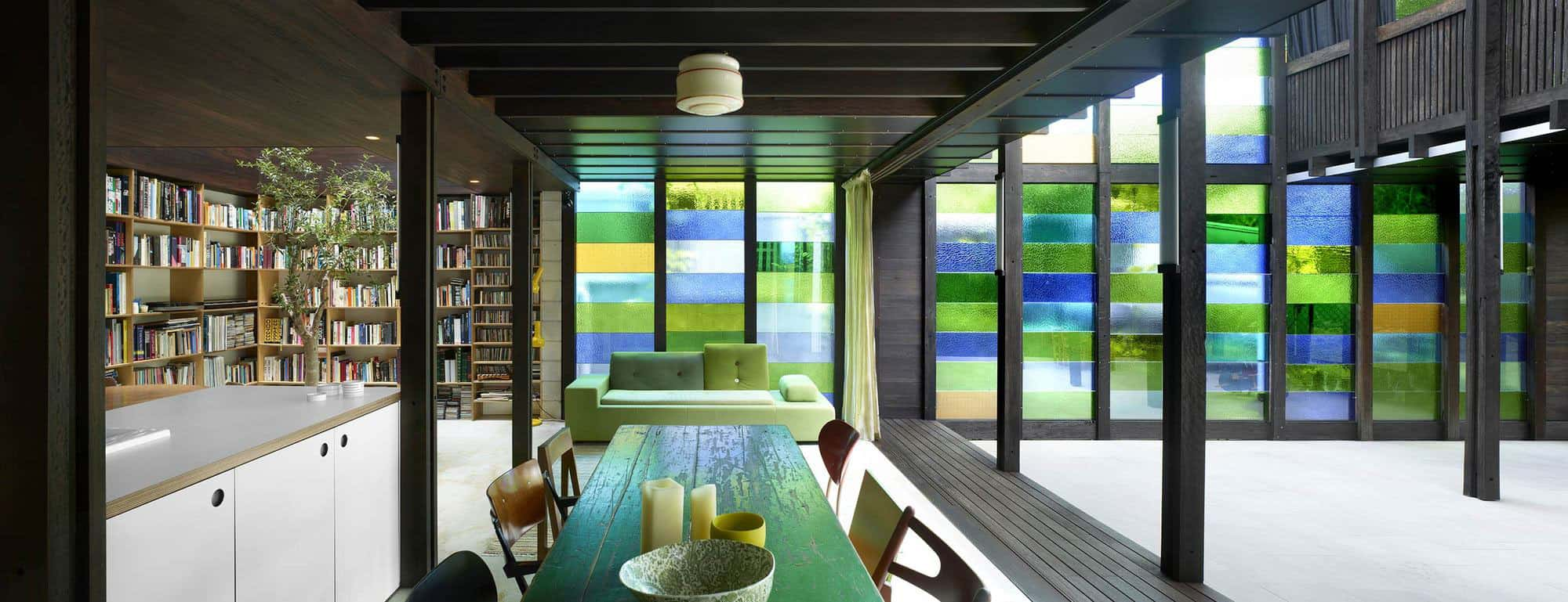 Cottage with Colored Glass Walls and Preexisting Trees