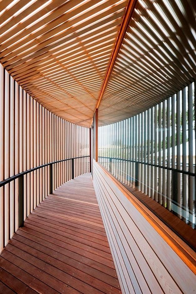 Rectangular Wooden House With Slatted Circular Facade