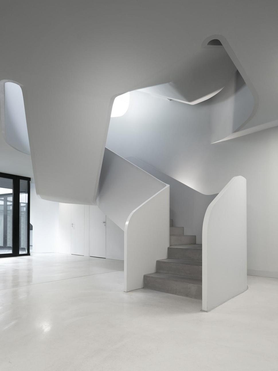 Angular Modern Home Features Large Curvaceous Stairwell Inside