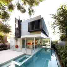 House With Outdoor Spiral Staircase Leading Rooftop Deck