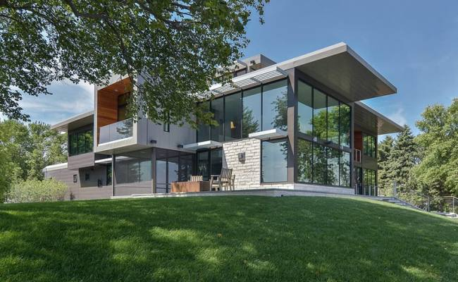 Glass Lake House Features Modern Silhouette Of Earthy