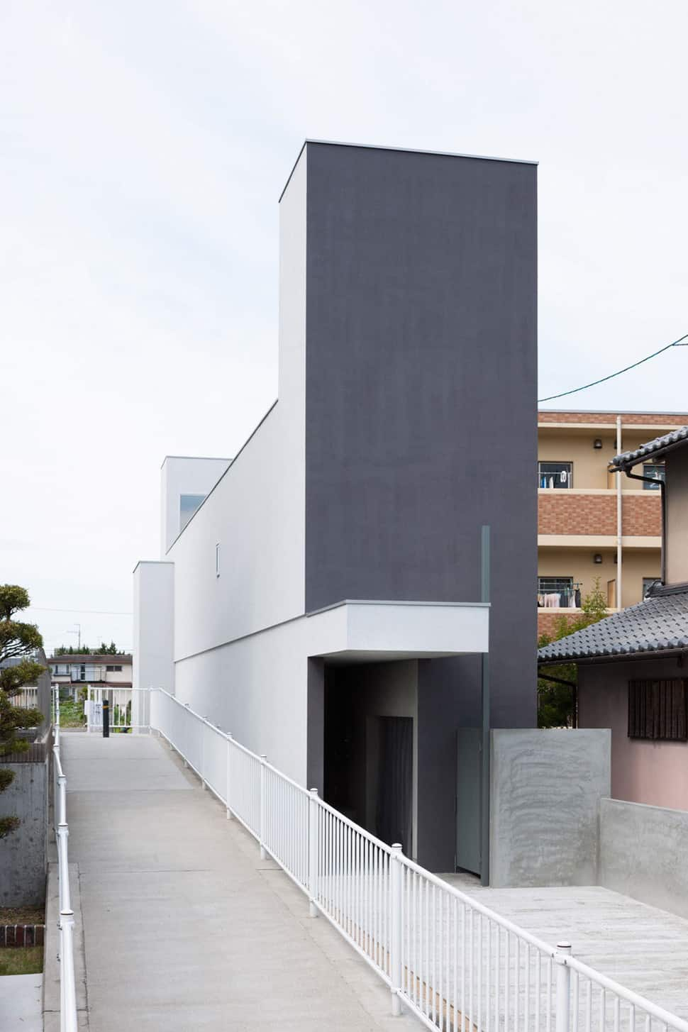 Narrow urban home with concrete walls and upper bridge