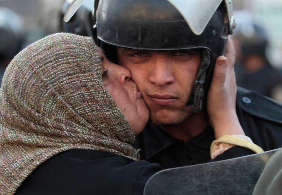Mujer-egipcia-besa-a-un-policía-durante-la-revolución-del-gobierno-de-Mubarak.-Egipto,-2011