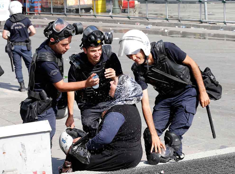 Policías-ayudan-a-mujer-afectada-por-el-gas-lacrimógeno.-Ankara,-Turquía,-2013.