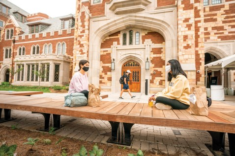Students sit outside the recently completed Nicholas S. Zeppos College.