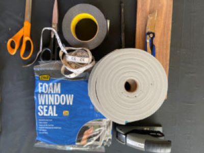Materials and tools being used to make face masks, including scissors, measuring tape, duct tape, adhesive foam, packages of window seal, a stapler, a box cutter, and a block of wood.