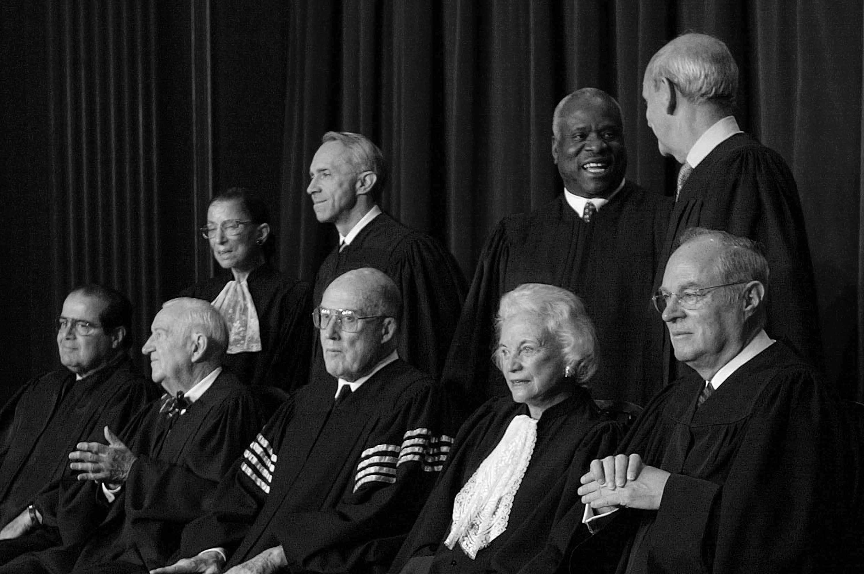 (L-R, Seated) Associate Justice Antonin Scalia, Associate Justice John Paul Stevens, Chief Justice William H. Rehnquist, Associate Justice Sandra Day O'Connor, Associate Justice Anthony M. Kennedy, (L-R, Standing) Associate Justice Ruth Bader Ginsburg, Associate Justice David H. Souter, Associate Justice Clarence Thomas and Stephen G. Breyer pose for pictures at the US Supreme Court in 2003 (Photo by Mark Wilson/Getty Images)