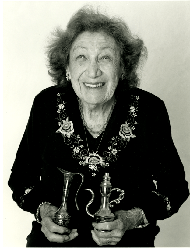 One exhibit photograph: Ruth (Gerda) Seelig Hirsch, holding Arabic teapots from her life in Israel. (Photo courtesy of the exhibit)