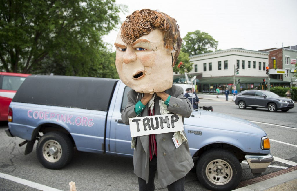 A CodePink protester puts on his Donald Trump head before the start of a small protest outside of the RNC against Donald Trump in Washington for his meeting with Ryan. (Bill Clark/CQ Roll Call)