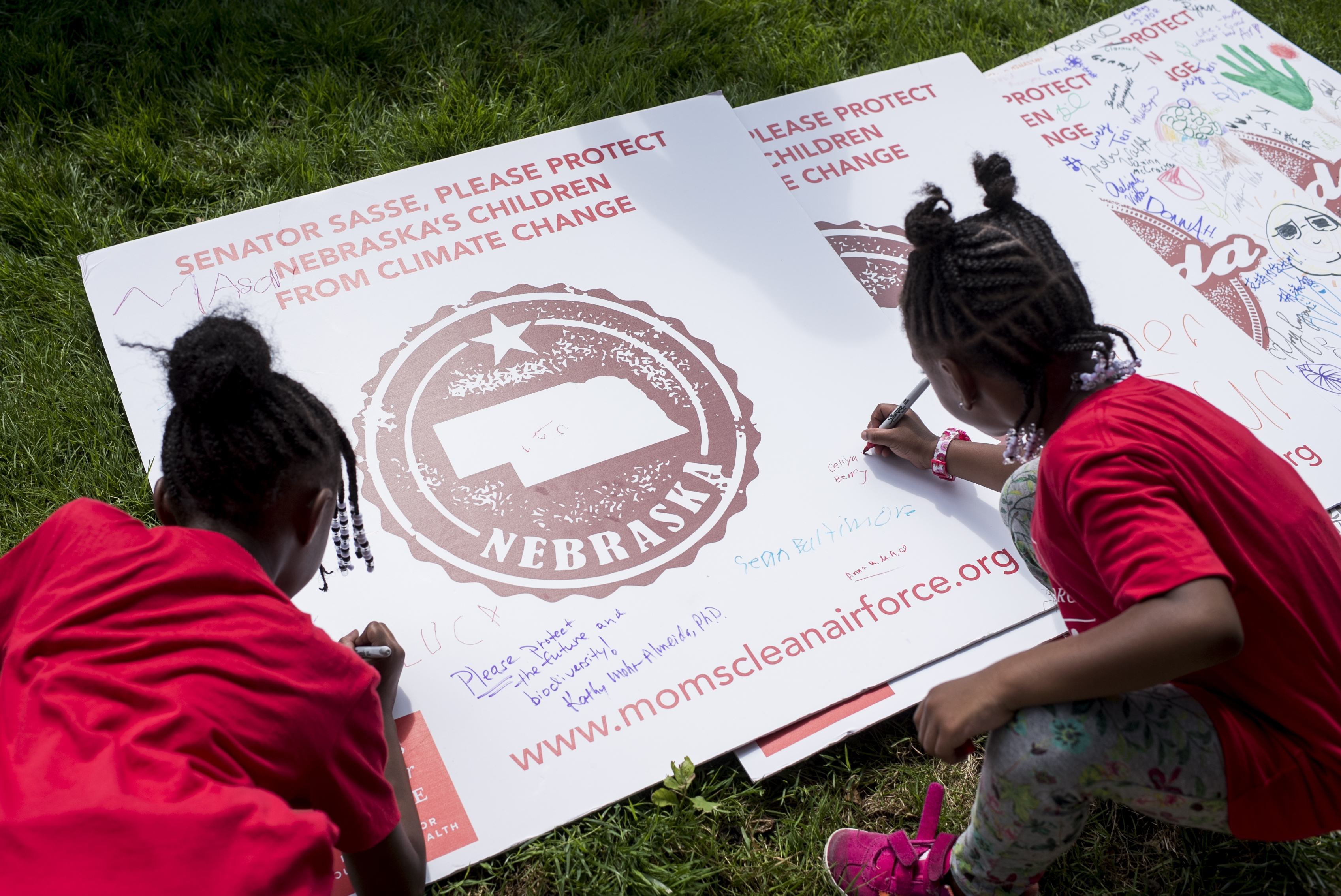 Kids write their names and decorate signs calling on senators to act on climate change legislation during the Moms Clean Air Force