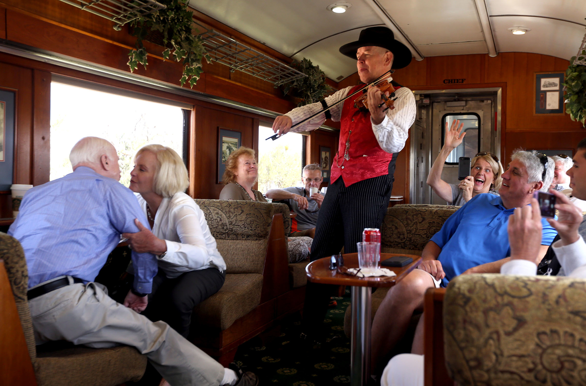 United States Senator John McCain, left, gets a kiss from his wife Cindy at the urging of the fiddle player as part of the entertainment on the train from Williams, Arizona to the Grand Canyon Wednesday. (Photograph by Daniel A. Anderson)