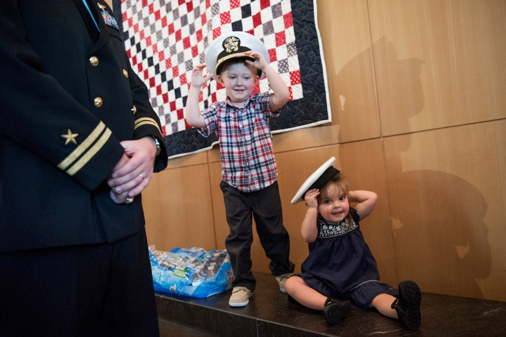 Pierson Kennedy, 4, and his sister Charlotte, 2, play with Navy covers after a graveside service for Women Airforce Service Pilot (WASP) Elaine Harmon, at Arlington National Cemetery, Sept. 7, 2016. (Tom Williams/CQ Roll Call)