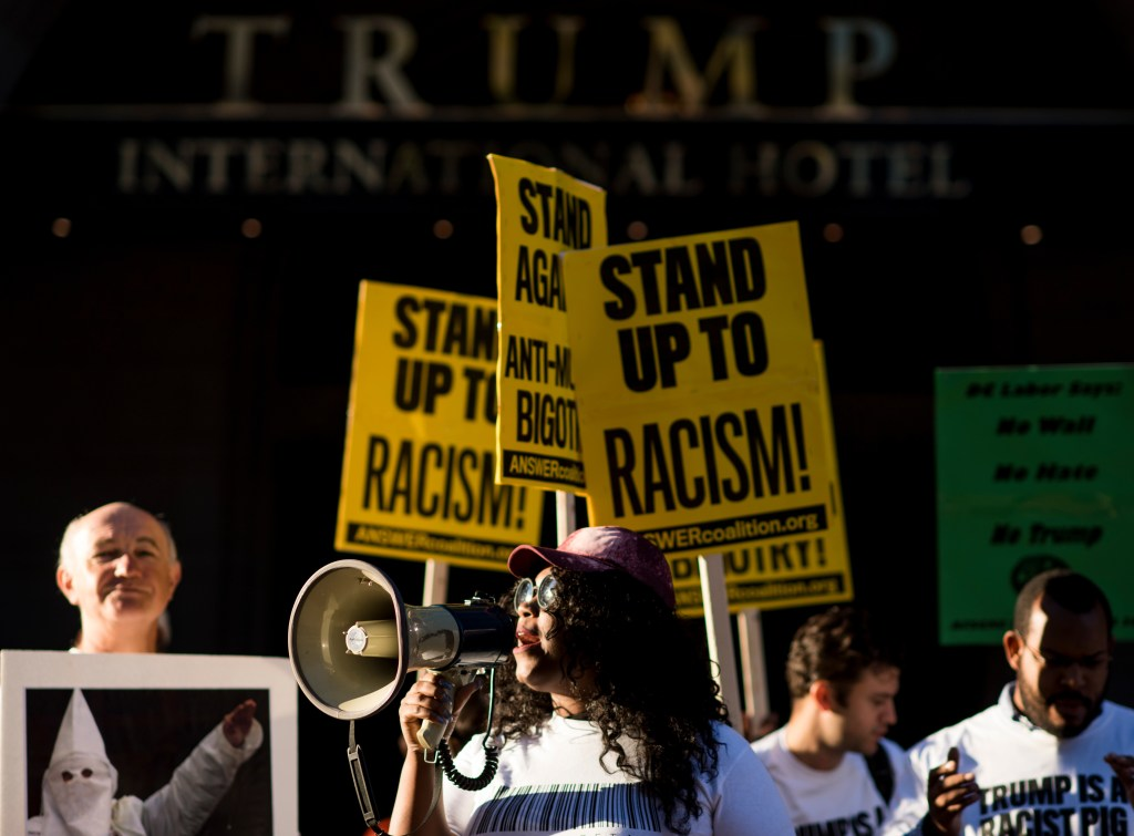Demonstrators from the ANSWER Coalition rally in front of the Trump International Hotel on Monday. (Bill Clark/CQ Roll Call)