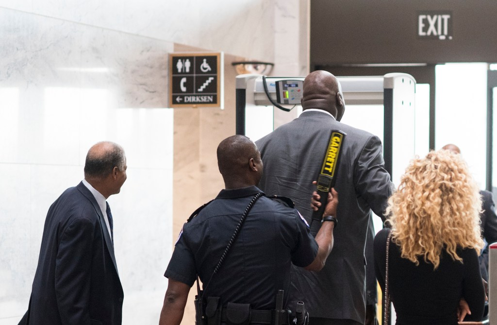 O''Neal is wanded by Capitol Police after he set off ametal detector while enteringthe Hart Senate Office Building. (Bill Clark/CQ Roll Call)