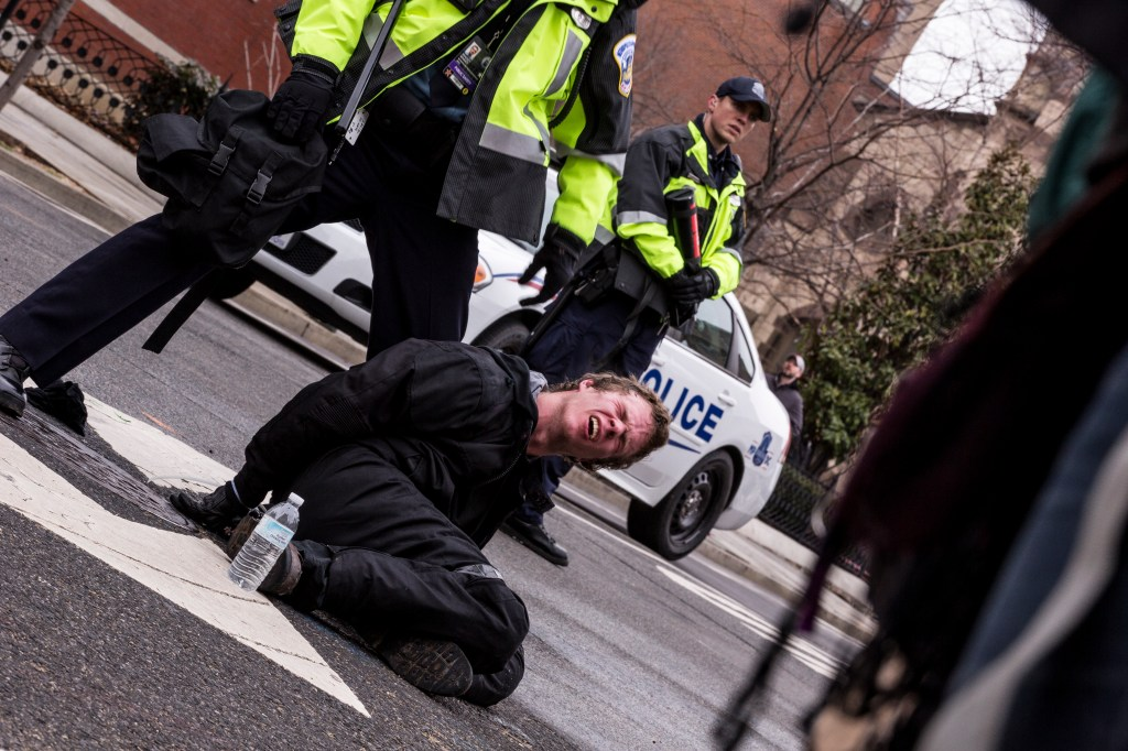 A protester is detained shortly after being pepper-sprayed in downtown Washington on 11th Street. (Matt Rhodes for CQ Roll Call)