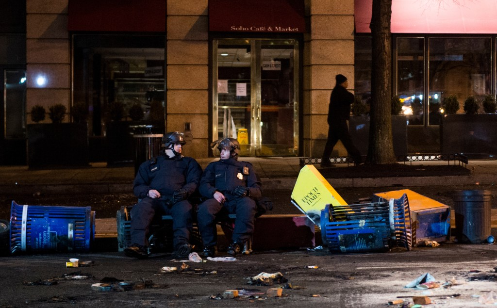 UNITED STATES - JANUARY 20: Two police officers in riot gear rest amid burned trash cans and newspaper boxes on the 1300 block of K Street NW in Washington following a day of unrest stemming from the Inauguration of Donald Trump as the 45th President of the United States on Friday, Jan. 20, 2017.(Photo By Bill Clark/CQ Roll Call)