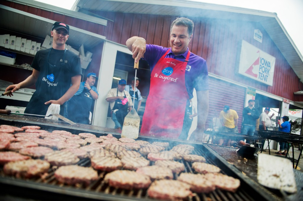 Braley helps out on the grill in the Pork Tent at the 2014 Iowa State Fair. (Tom Williams/CQ Roll Call)