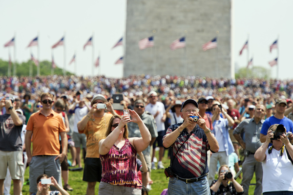 Spectators watch World War II era aircraft as they fly over the World War II Memorial. (Tom Williams/CQ Roll Call)