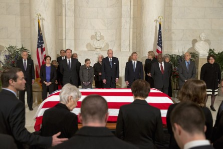 The family of late Supreme Court Justice Antonin Scalia take their seats as Supreme Court Justices stand for a private ceremony in the Great Hall of the Supreme Court in Washington, Friday, Feb. 19, 2016, where Scalia will lie in repose. From back left are Counselor to the Chief Justice Jeffrey Minear, and Supreme Court Justices Elena Kagan, Samuel Anthony Alito, Jr., Ruth Bader Ginsburg, Anthony M. Kennedy, Chief Justice John G. Roberts, Jr., Clarence Thomas, Stephen G. Breyer, and Sonia Sotomayor.  (AP Photo/Jacquelyn Martin, Pool)