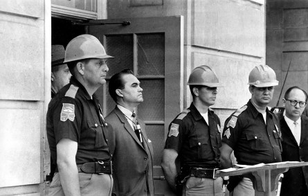 FILE - In this June 11, 1963 file photo, Gov. George Wallace blocks the entrance to the University of Alabama as he turned back a federal officer attempting to enroll two black students at the university campus in Tuscaloosa, Ala. Wallace backed down when President John Kennedy federalized the Alabama National Guard and ordered troops to Tuscaloosa. Wallace's daughter, Peggy Wallace Kennedy, said her family has lived in the shadow of the schoolhouse door ever since. She said her father never told her why he did it and she never asked him before he died in 1998. Since then, she has been involved in civil rights events in Alabama. She wants to give hope to people by showing that families can change.  (AP Photo/File)