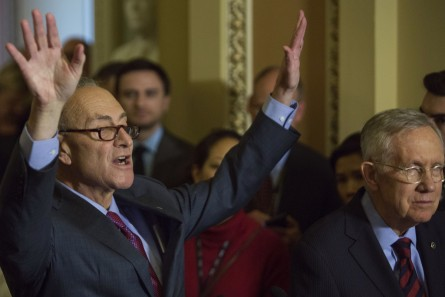 UNITED STATES - DECEMBER 8 - Sen. Chuck Schumer, D-N.Y., raises his arms as he speaks alongside Senate Minority Leader Harry Reid, D-Nev., during the weekly Senate Democrat luncheon news conference on Capitol Hill in Washington, Tuesday, December 8, 2015. (Photo By Al Drago/CQ Roll Call)