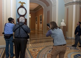 Journalists take photos of the Ohio Clock shortly after midnight on Oct. 1, the beginning of the shutdown. The clock has not been wound, due to the shutdown, as the winders have been furloughed. (Douglas Graham/CQ Roll Call.)