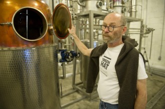 Michael Lowe, co-owner and distiller of New Columbia Distillers, shows of the still for