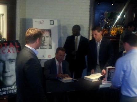 Arnold Schwarzenegger signing copies of