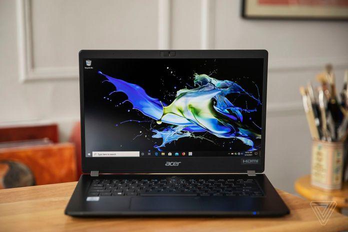O Acer Travelmate P6 visto aberto de frente. A tela exibe um padrão azul e amarelo em um fundo preto.