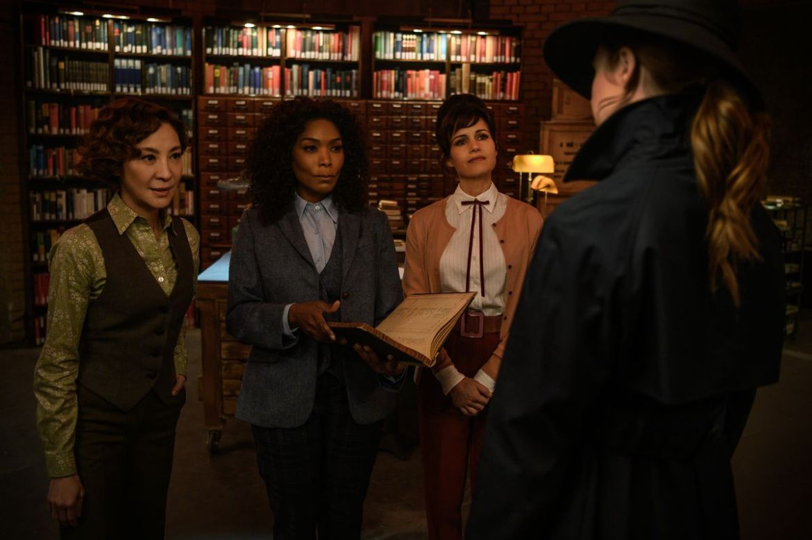 Karen Gillan, seen from behind and wearing a hat and trenchcoat, faces a panel of weaponeers—Michelle Yeoh, Angela Bassett, and Carla Gugino —in Gunpowder Milkshake