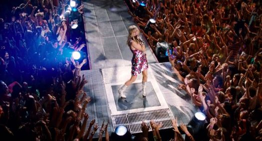 Miley Cyrus as Hannah Montana performs on a thrust stage surrounded by a crowd in Hannah Montana