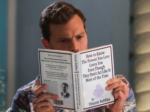 Jamie Dornan as Edgar reading a book called How to Know the Person You Love Loves You Even Though They Don't Act Like It Most of the Time in Barb & Star Go to Vista Del Mar