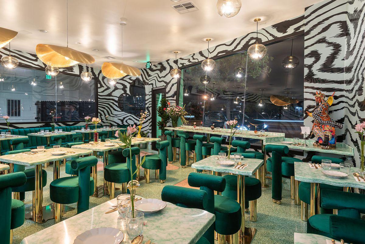 Un elegante comedor de noche con sillas de terciopelo verde y empapelado vertiginoso.