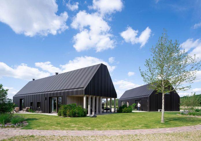 Два черных одетых строения рядом друг с другом. Один из левых имеет белые колонны, оба немного похожи на амбары, установленные в траве.