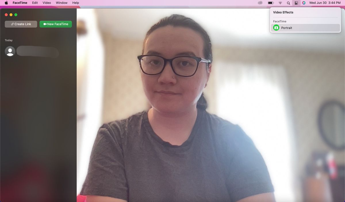 A screenshot of a MacBook screen where a user is on a FaceTime call with a blurred bright bedroom background. A FaceTime drop-down menu is open in the top right with Portrait selected.