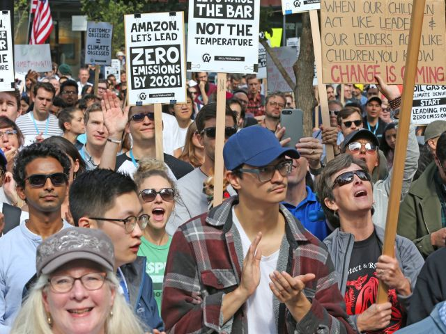 A crowd of Amazon employees holding signs about climate change participate in a global climate strike.