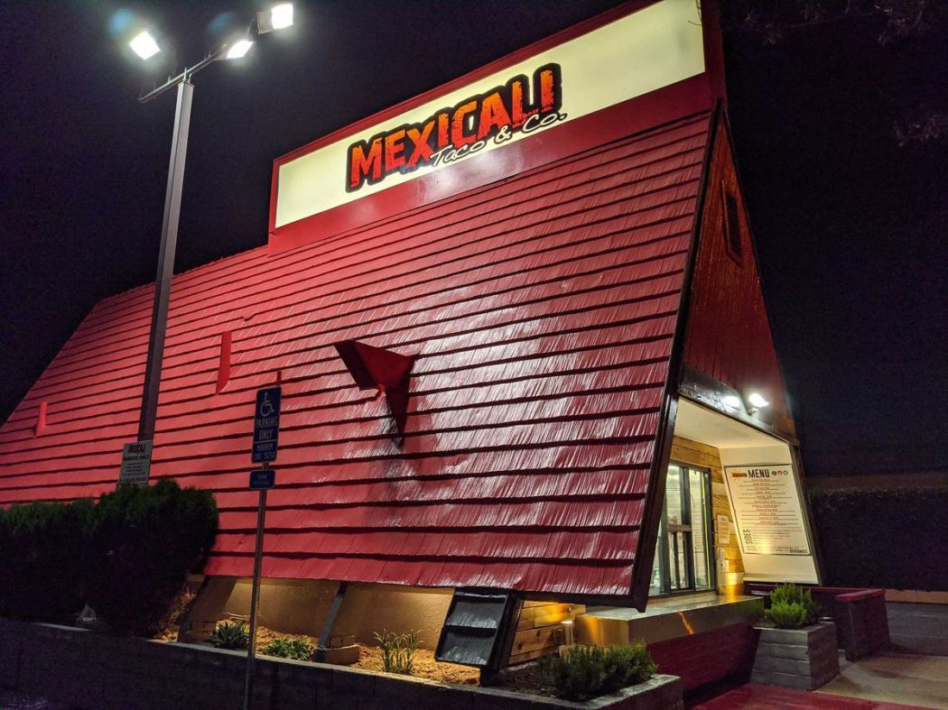A pitched red roof with a sign for a taco restaurant, shown at night.