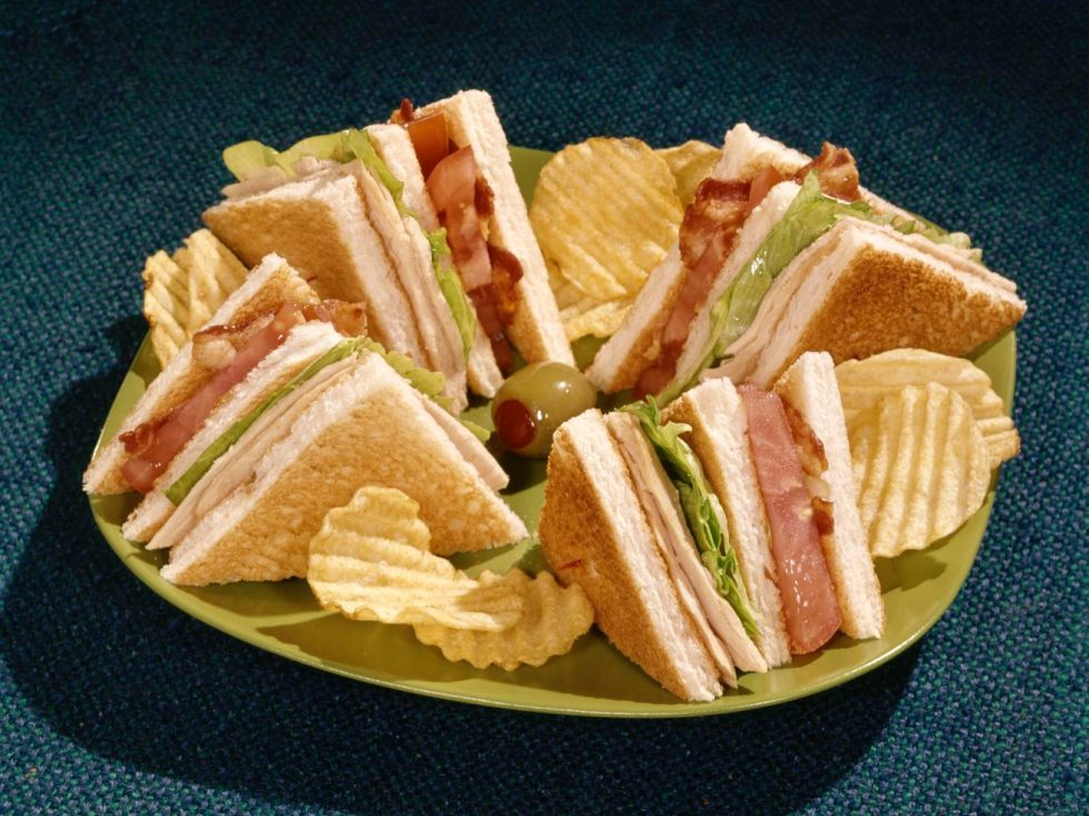 A vintage photo of a club sandwich, cut into triangular wedges, with olives and potato chips