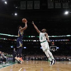 Utah Jazz's Donovan Mitchell, center left, shoots over Boston Celtics' Kemba Walker (8) during the first quarter of an NBA basketball game Friday, March 6, 2020, in Boston.