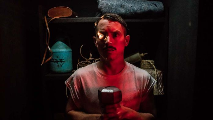 Elijah Wood holds a flashlight up to his eyes